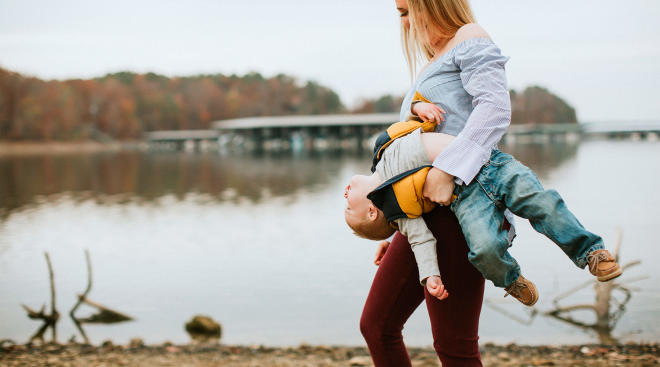 mom carrying her child in a funny way