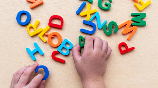 toddler hands playing with alphabet letters