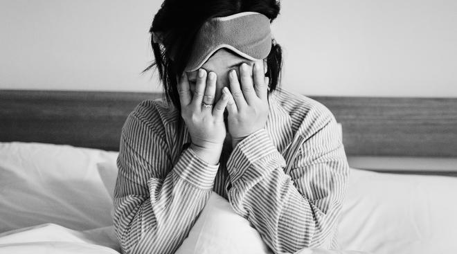 depressed woman in bed with hands over her face