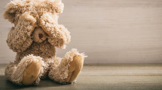 sad stuffed animal bear covering its eyes