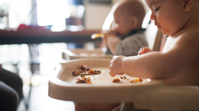 baby eating solid food at home in high chair