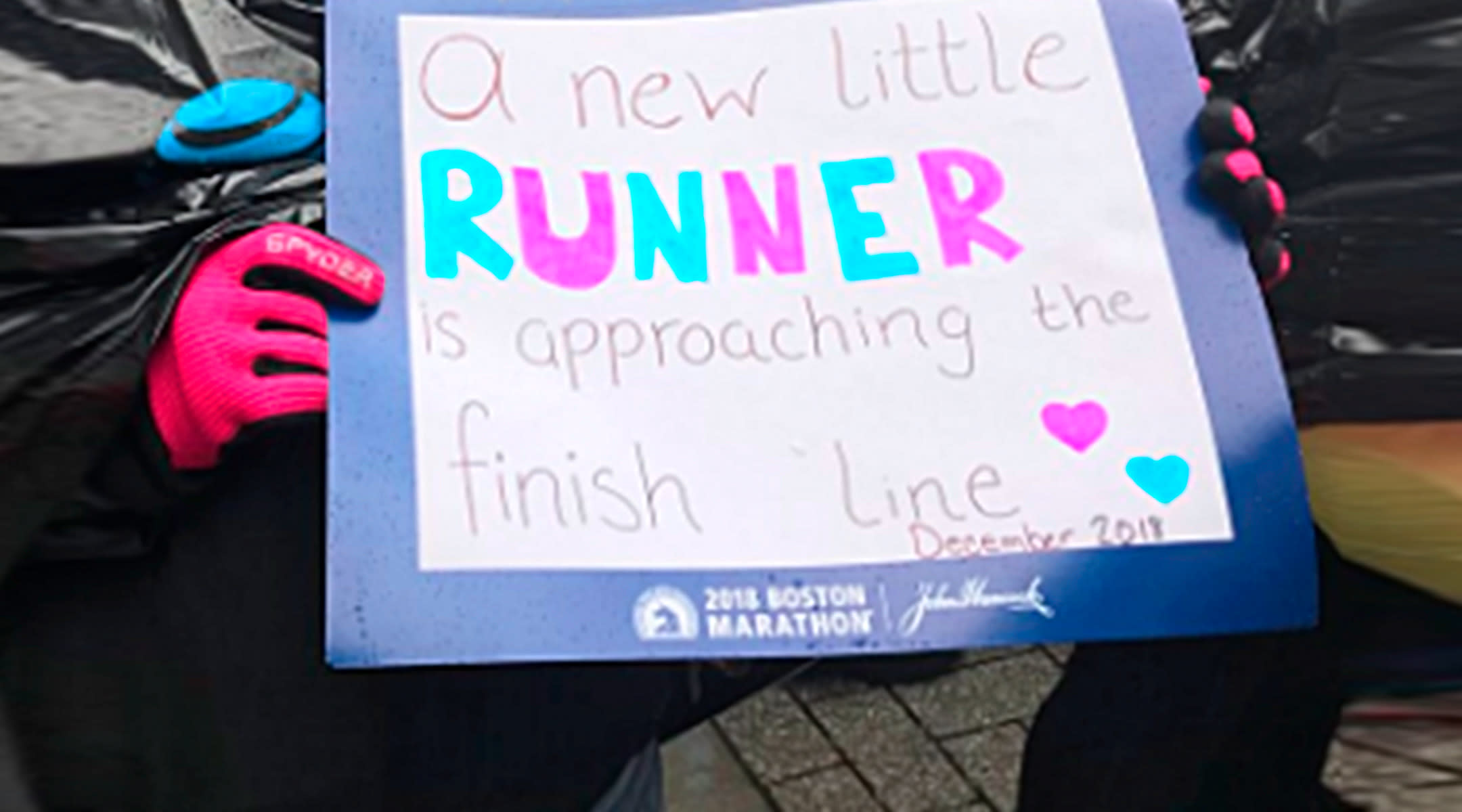 woman surprising her husband with pregnancy announcement at boston marathon