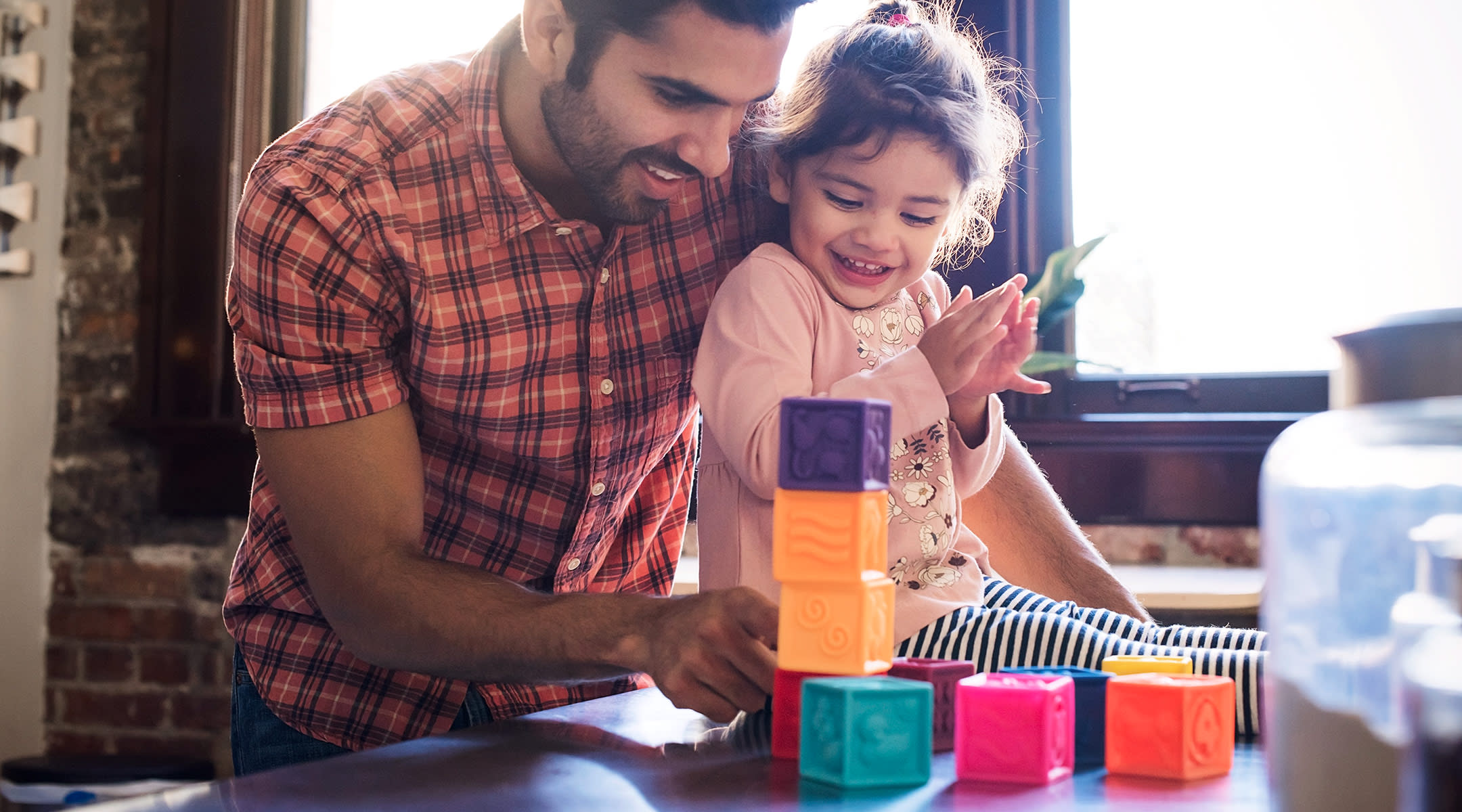 dad playing blocks with his daughter at home on the weekday