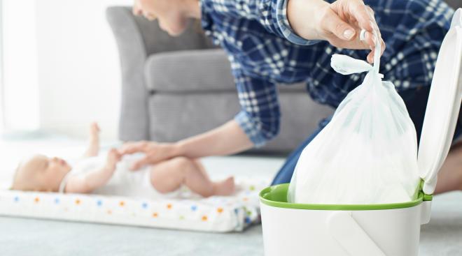 mom placing plastic bag in diaper pail