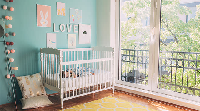 baby nursery decorated with art and baby sleeping in her crib
