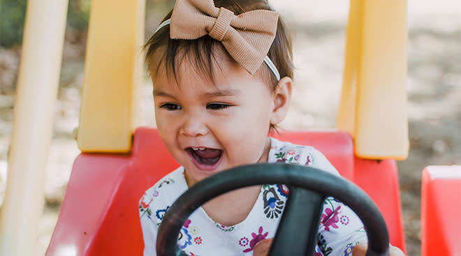 Happy toddler with bow in her hair drives toy car.