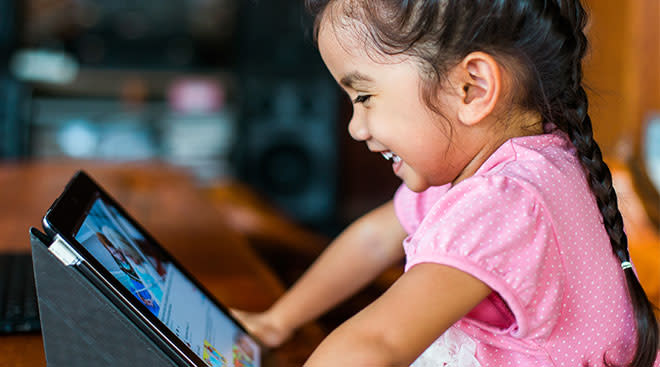 happy little girl watching tablet