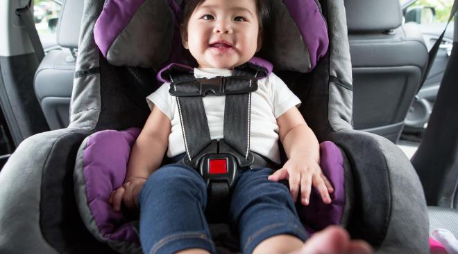 happy baby sitting inside car in a car seat
