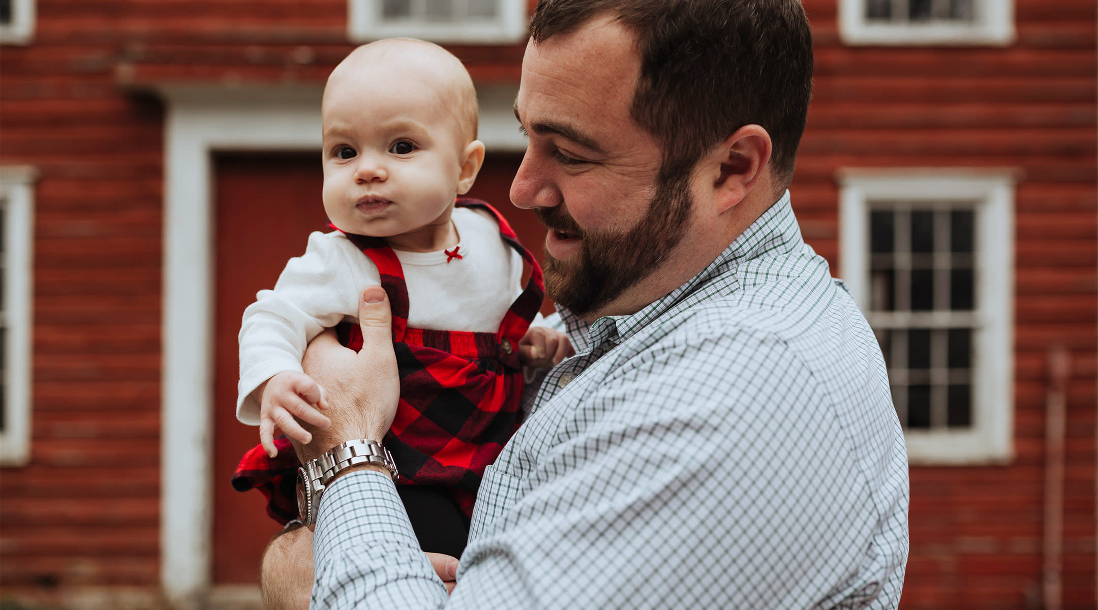 dad holding his baby who is dressed in a holiday outfit