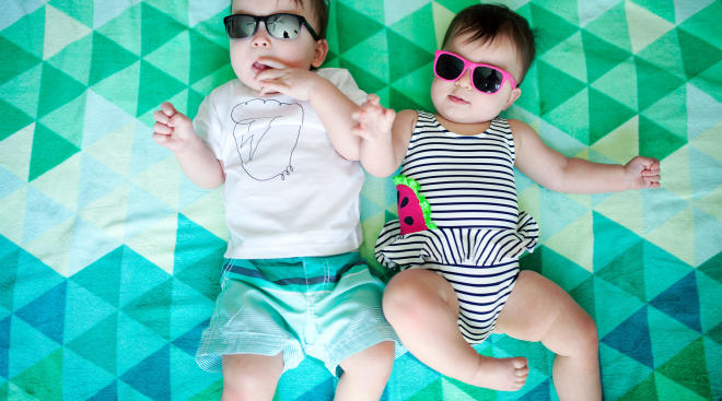 toddler and baby laying on beach towel wearing sunglasses