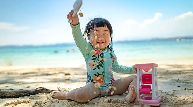 Happy toddler girl plays with a toy in the sand at the beach.
