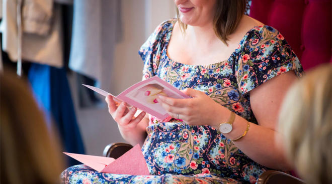 pregnant woman at her baby shower reading card
