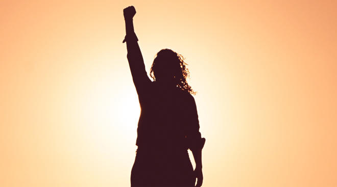 woman shot as silhouette against yellow sun in powerful stance with her arm raised