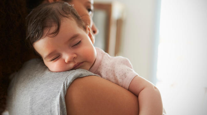 tired baby with fever rests on mom's shoulder