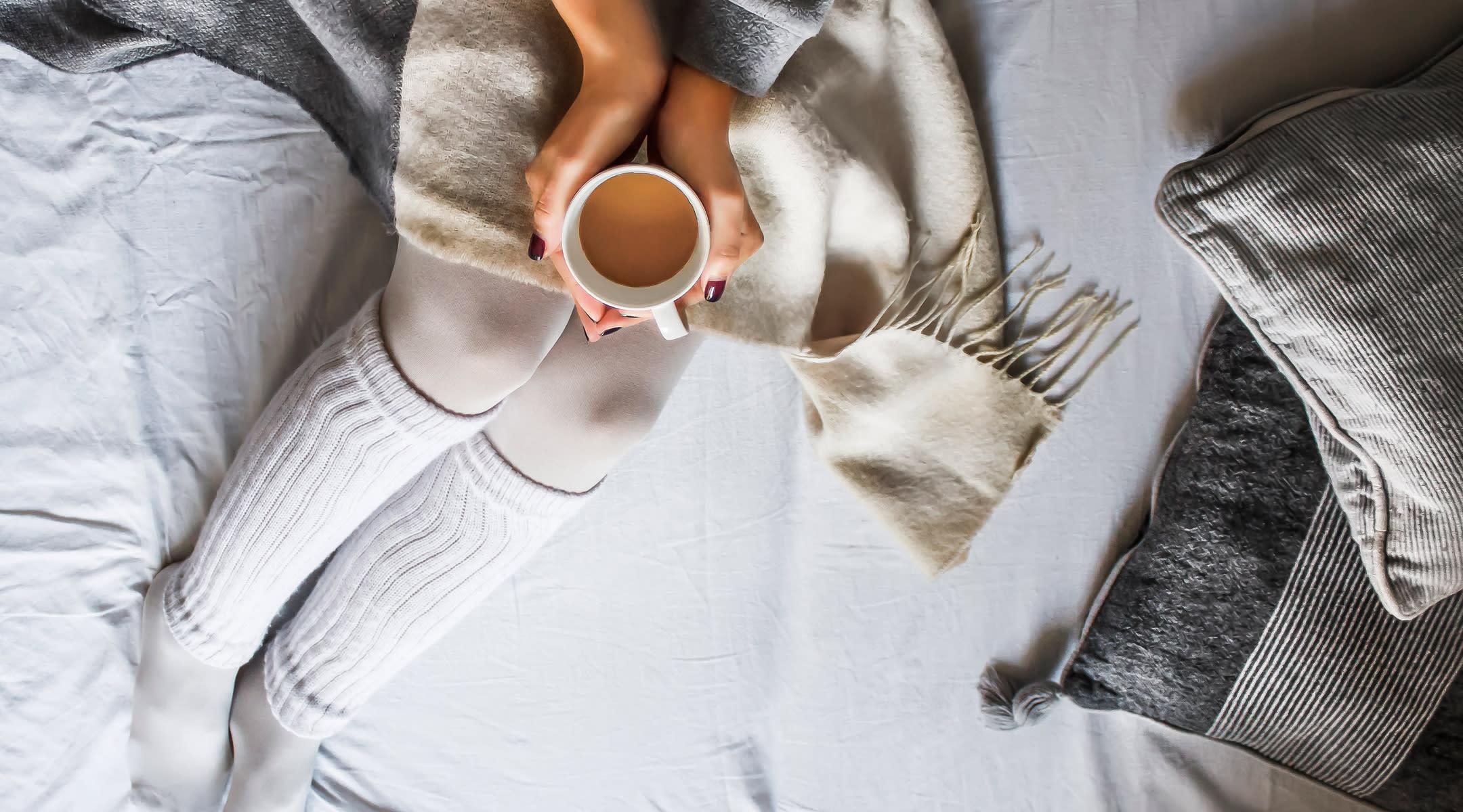 sick woman legs bed tea cup