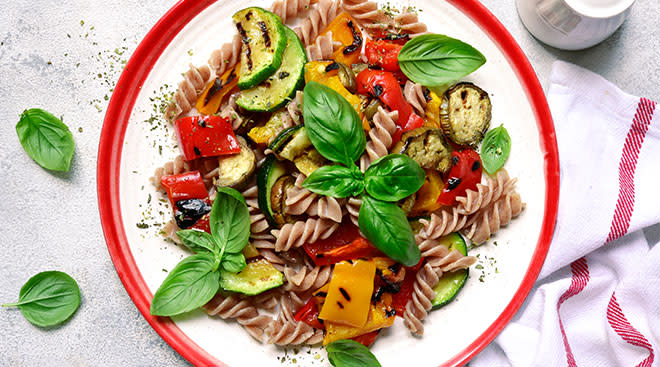 Whole wheat pasta with vegetables on a dinner plate.