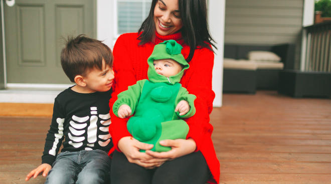 mom with her two kids in halloween costumes on the front porch