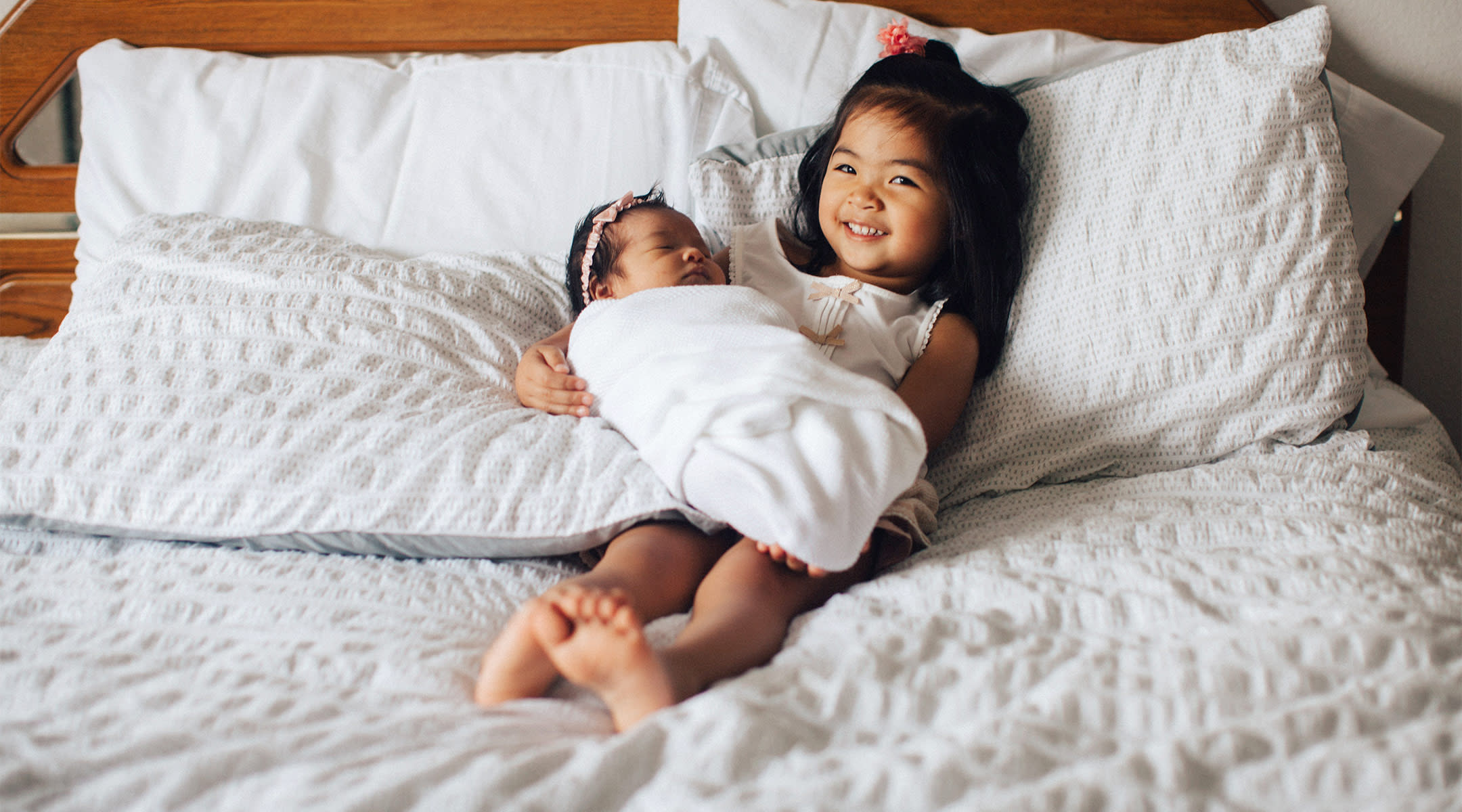 older sibling happily holding her newborn sister