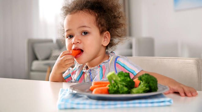 toddler eating a healthy snack, carrots and broccoli