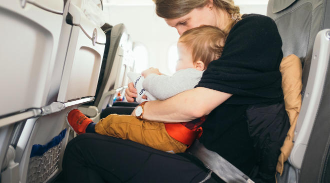 mom on airplane sitting with her baby