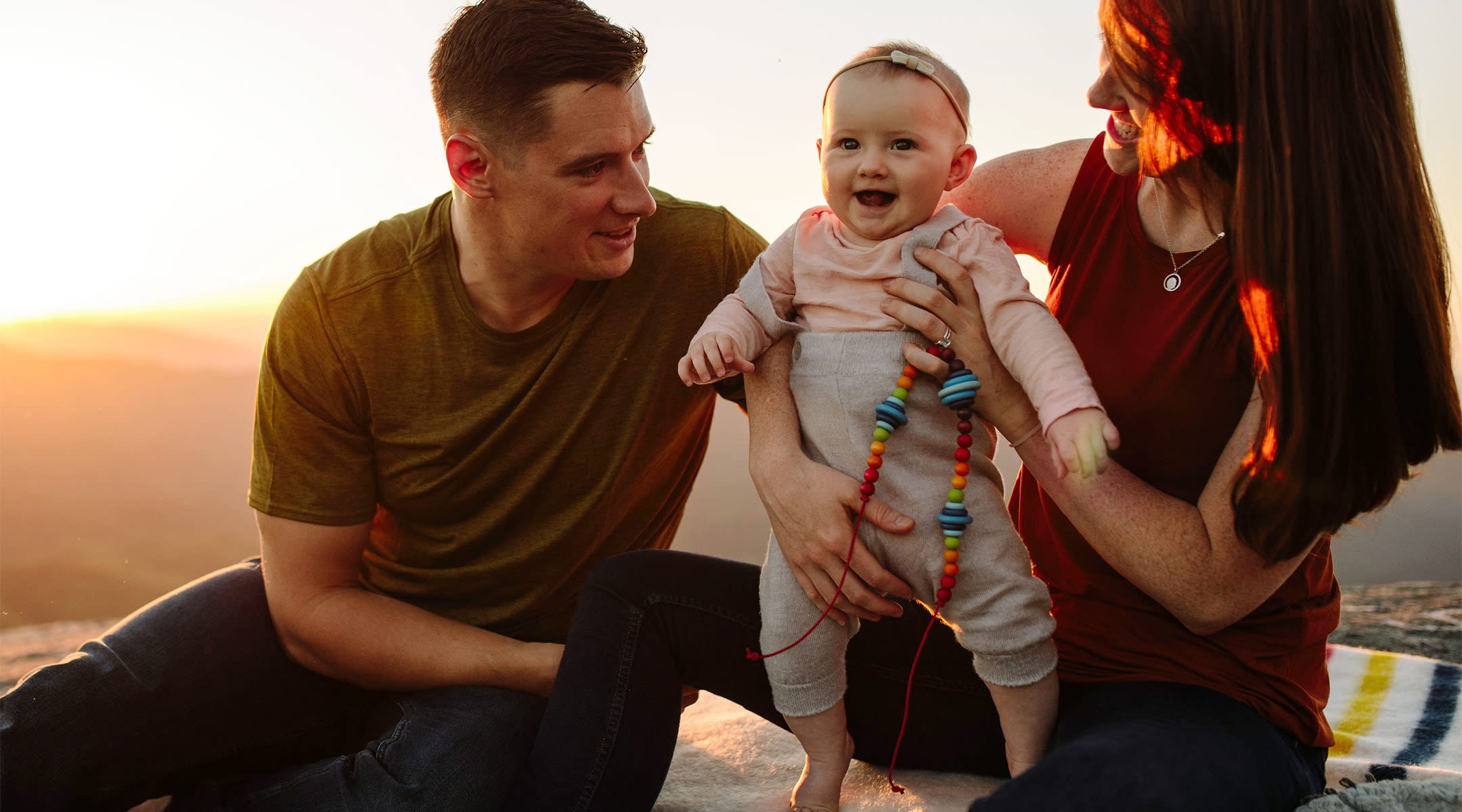 parents holding up their laughing baby while outdoors