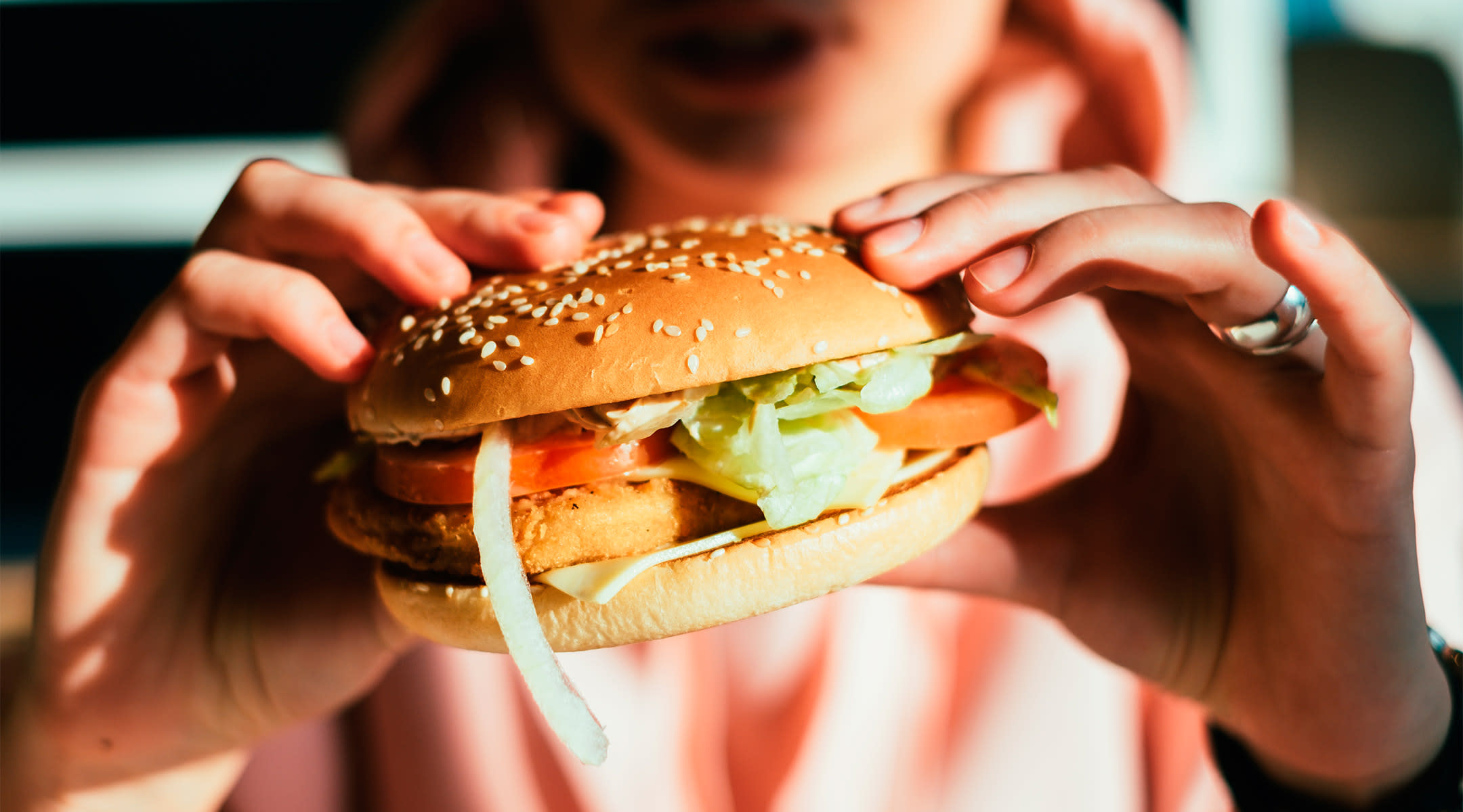 woman holding fast food burger