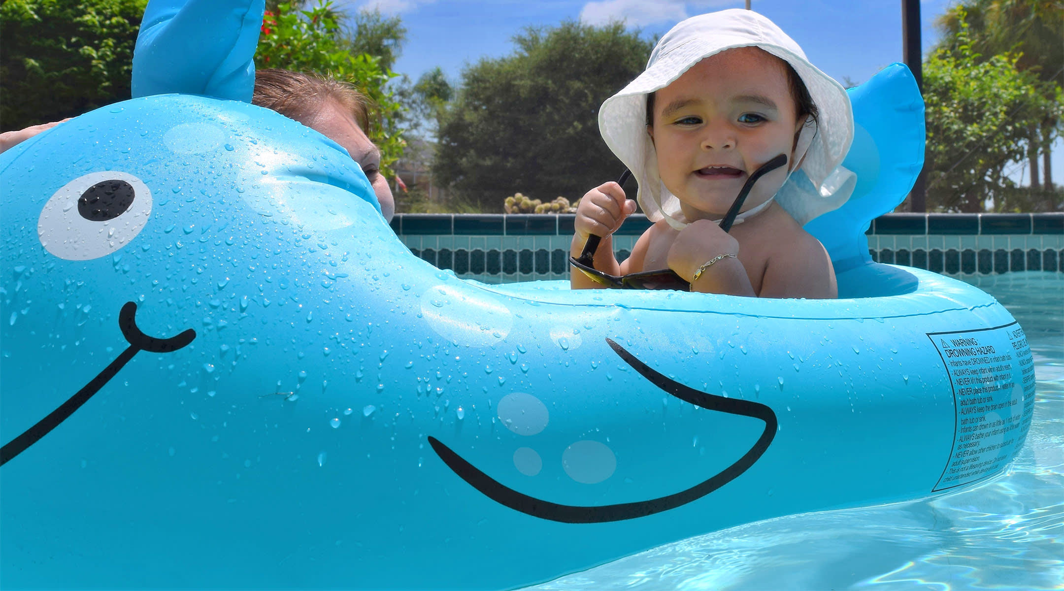 happy Baby swimming with a baby pool float