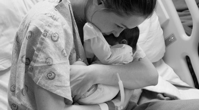 woman holds her newborn baby tightly after just giving birth
