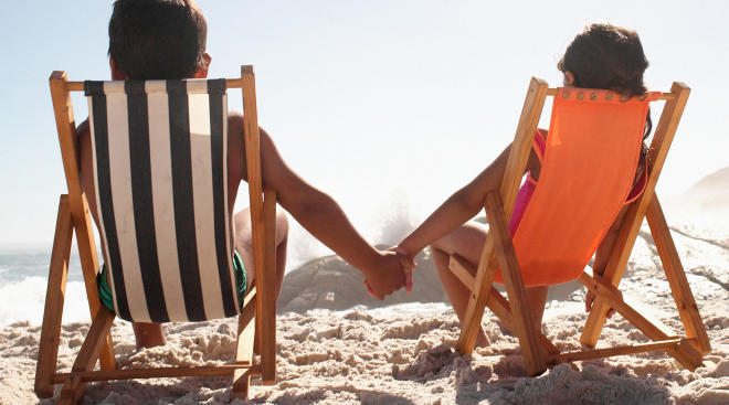 two children sitting at the beach on chairs and holding hands