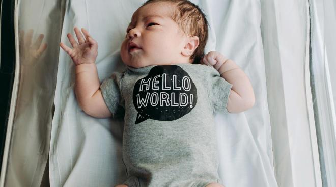 newborn baby in the hospital wearing a hello world onesie