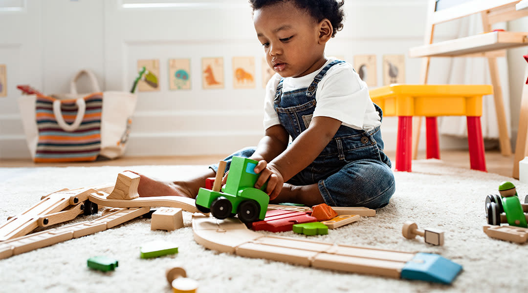 toddler playing in his room with wooden train set