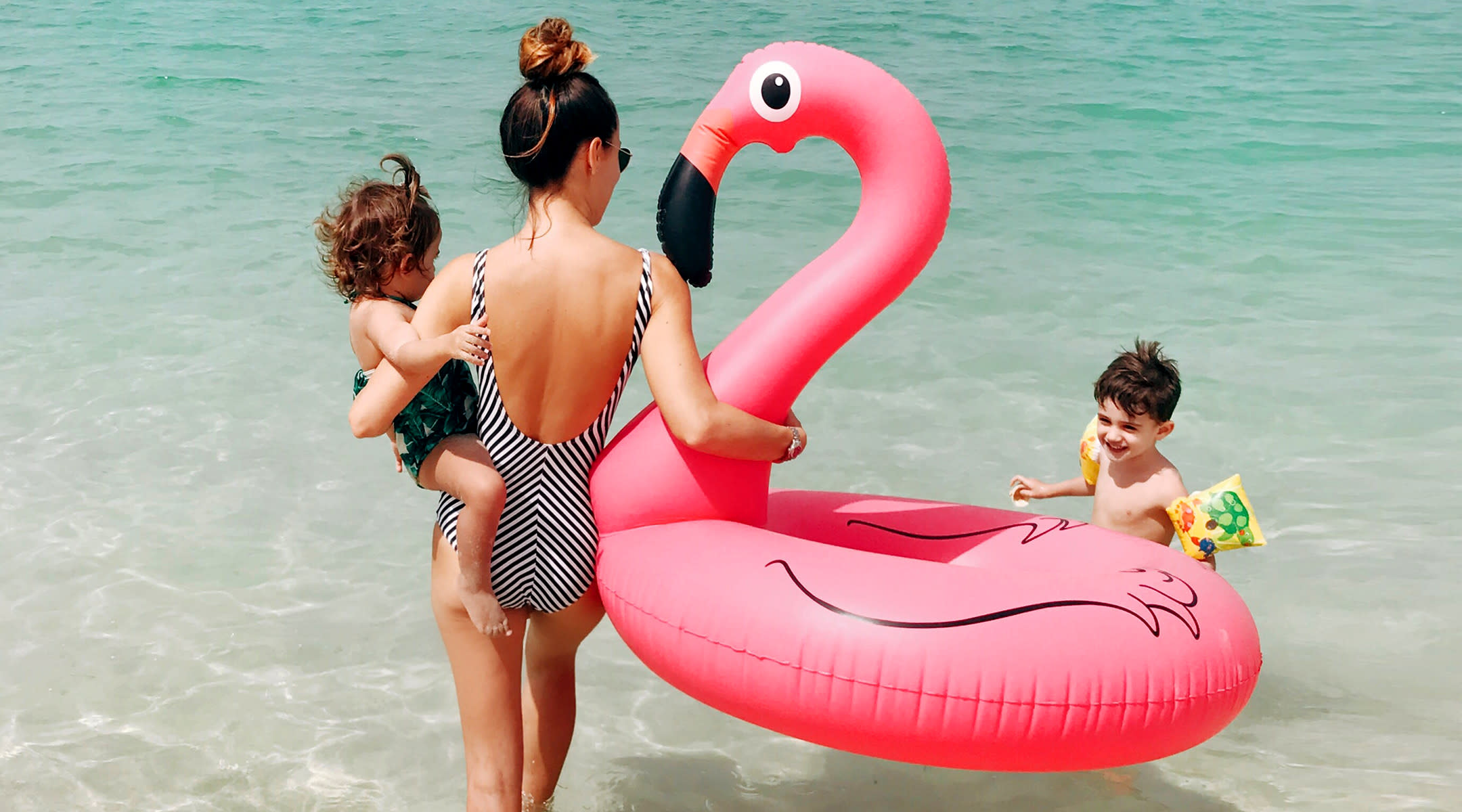 mom at beach traveling with her two young kids and holding a flamingo float