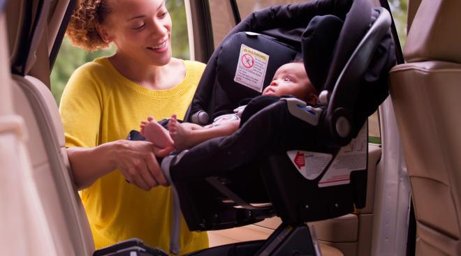 Mom putting newborn baby in car seat into car.