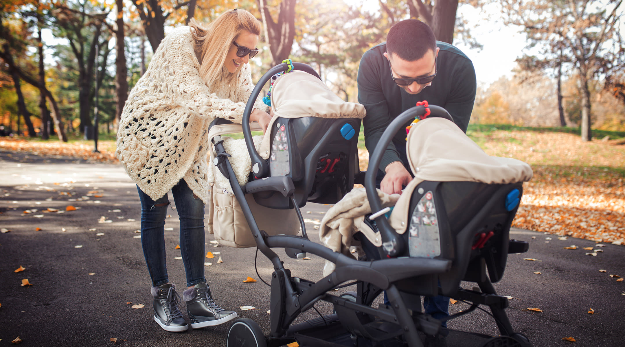 couple with double stroller in park