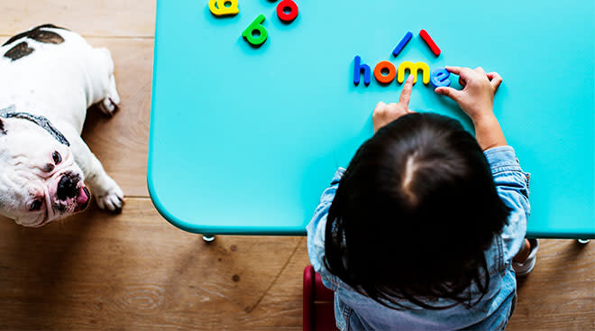 toddler at home playing with magnetic letters, spelling out home