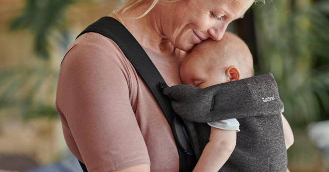 mom hugging baby in baby carrier