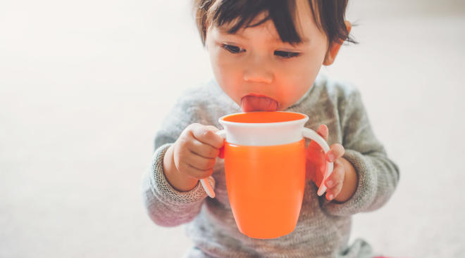 toddler licking orange sippy cup