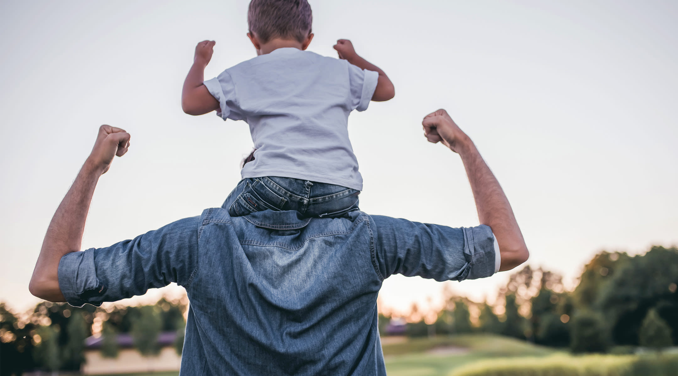 dad carrying toddler son on how shoulders, both strongly holding their arms out