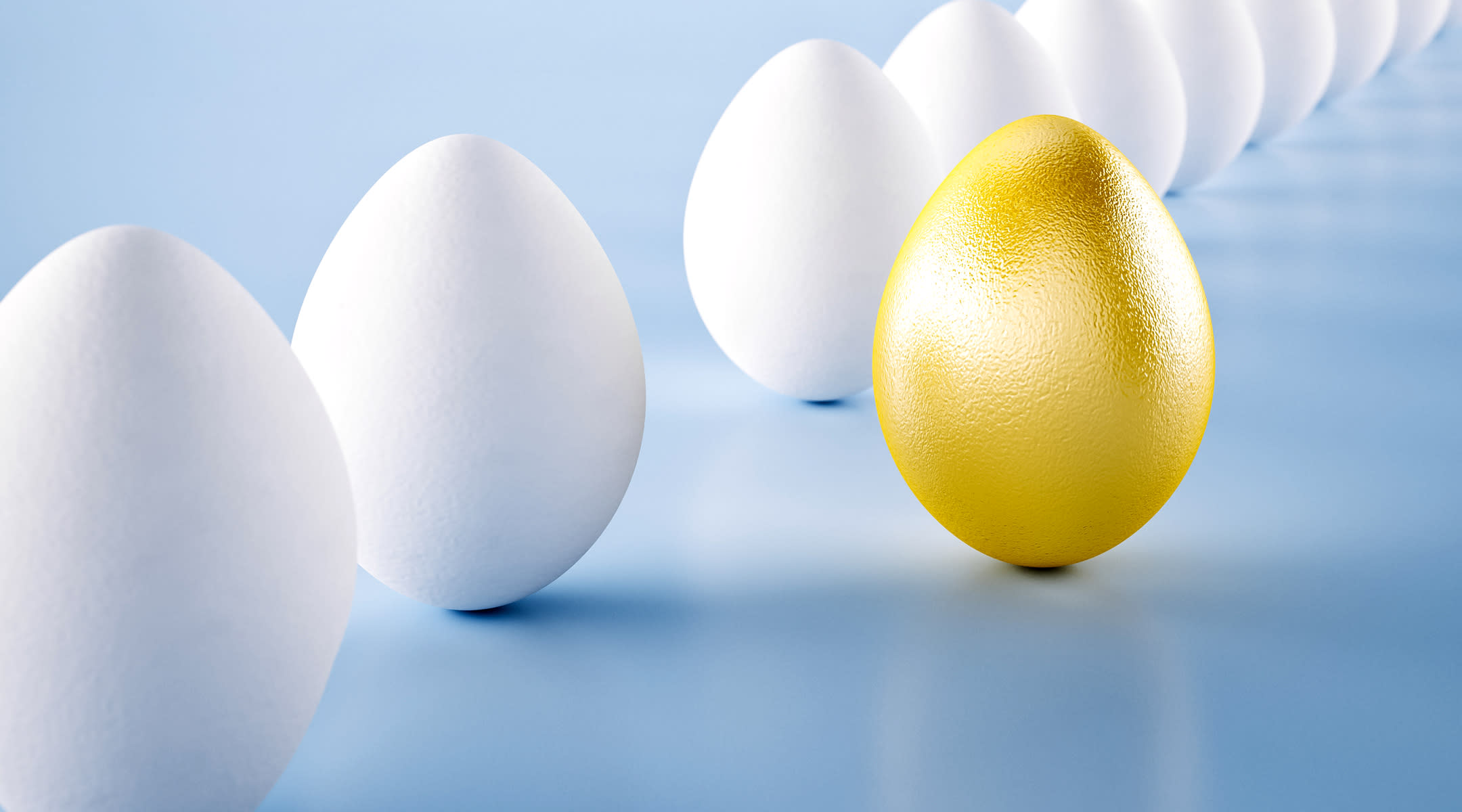 Eggs in repeating alignment with gold colored egg at the front of the frame.