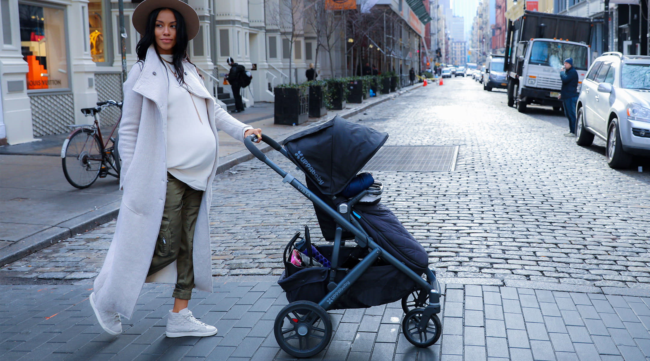 pregnant woman in urban environment crossing the street with stroller