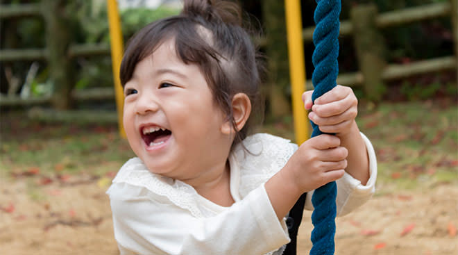 Little toddler girl swinging on rope swing at playground.