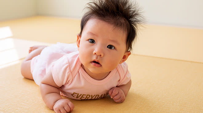 baby with lots of hair doing tummy time