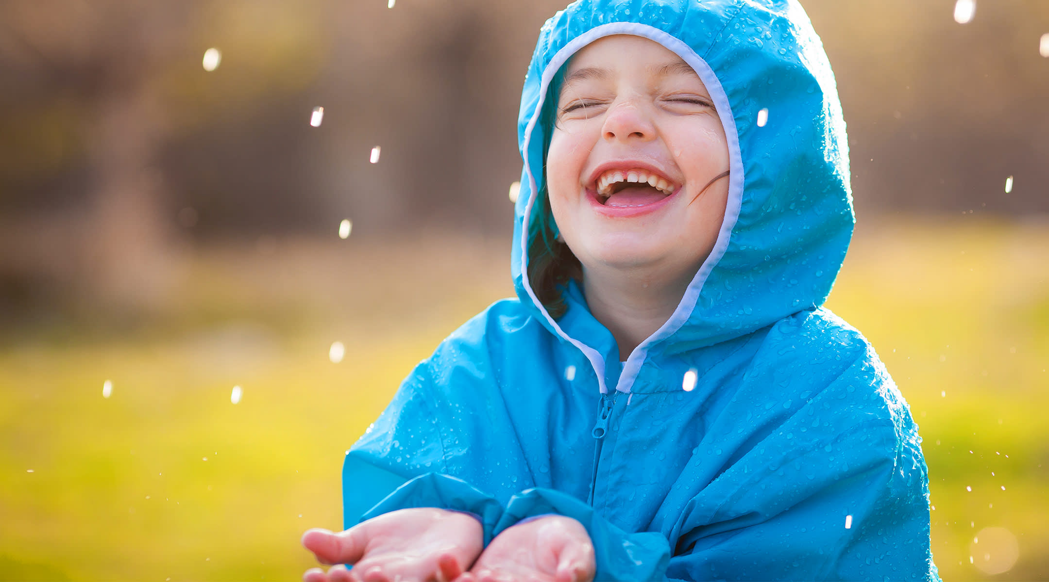 happy little girl in blue rain coat, playing in the rain