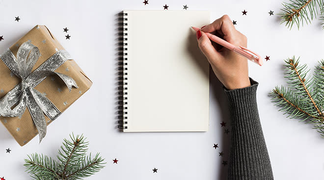 person's hand about to start writing holiday shopping list