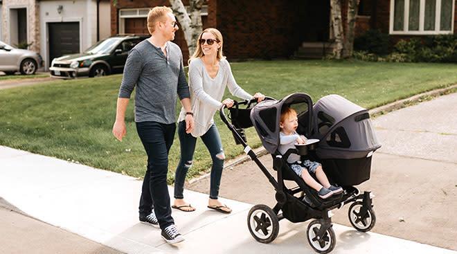 Parents pushing baby stroller through neighborhood.