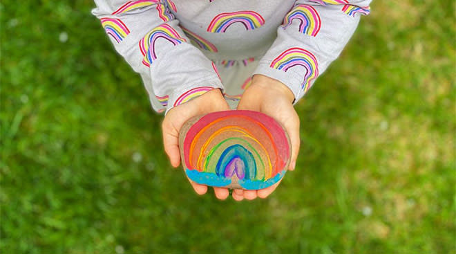 small child holding rainbow painted rock in support of covid-19