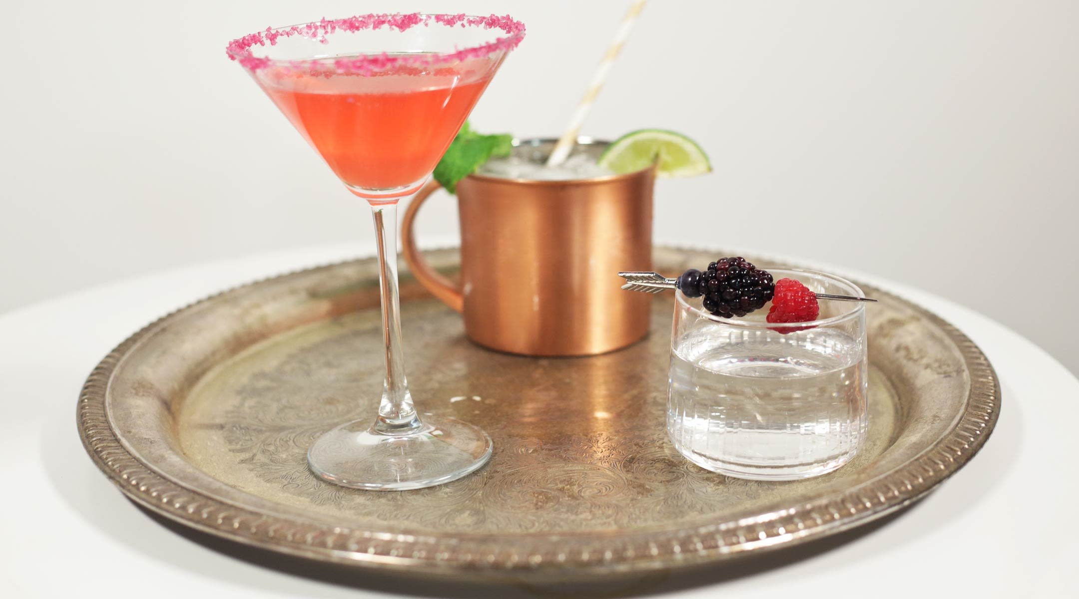 Photo of three different mocktails on silver serving tray.