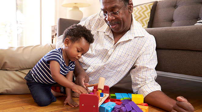 Grandparent playing blocks at home on the floor with his grandchild.