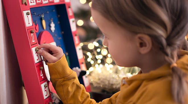 Little girl plays with advent calendar during the holiday season.