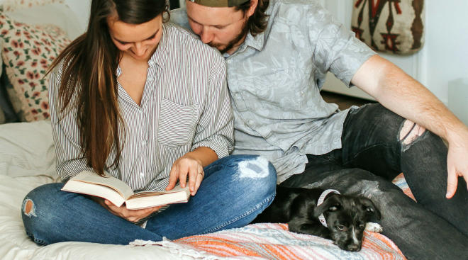 couple sitting on bed together reading a book with their puppy